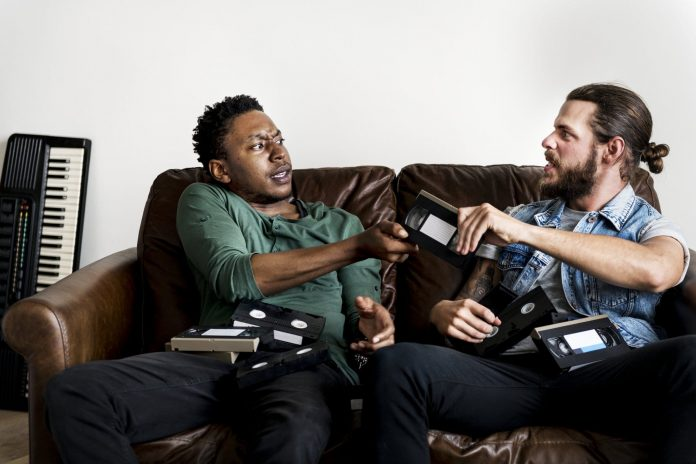 African American male and a Caucasian male hipsters fighting over VHS video tape