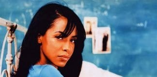 Aaliyah looking at the camera from the side wearing a blue top