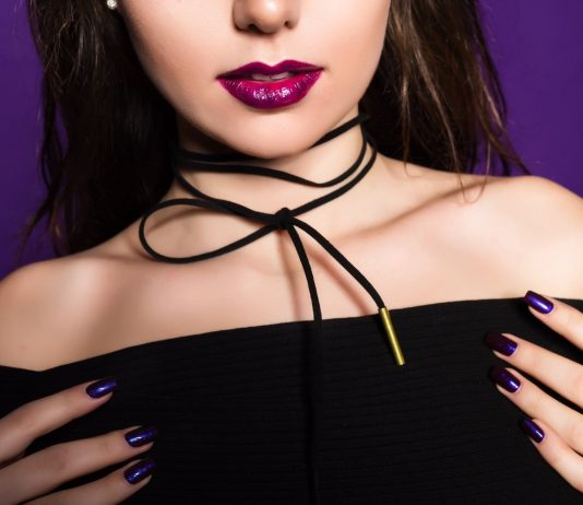 Grune fashion style a lady wearing choker and low cut black top with dark nail varnish