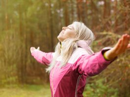 Woman with open arms wearing a pink windbreaker
