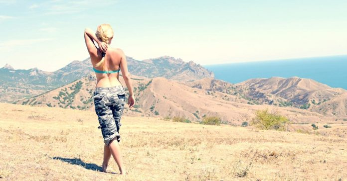 Woman walking in the hills wearing grey camo pants