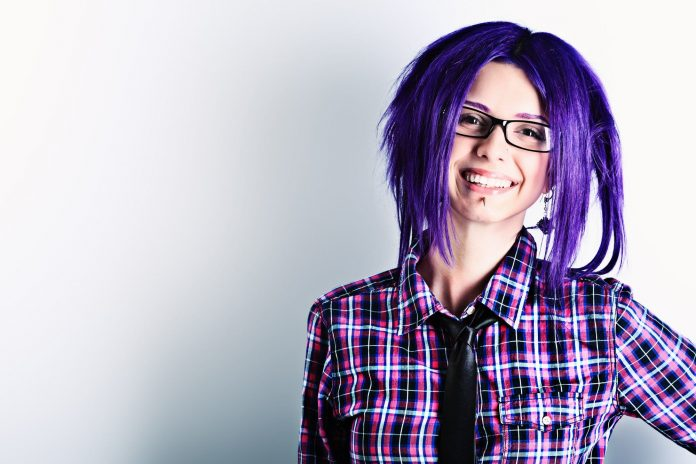 Emo punk girl with purple hair and black thick framed glasses wearing a stud and dangling earring, plaid shirt and black tie