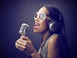 afro Caribbean woman singing into a microphone