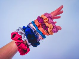 A woman's arm with at least 10 90s hair scrunchies