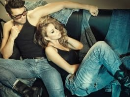 A man with black tank top wearing 90s style rugged blue jeans sitting with a woman wearing denim jeans