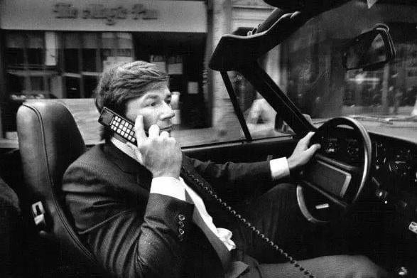business man driving with a car phone in the 90s