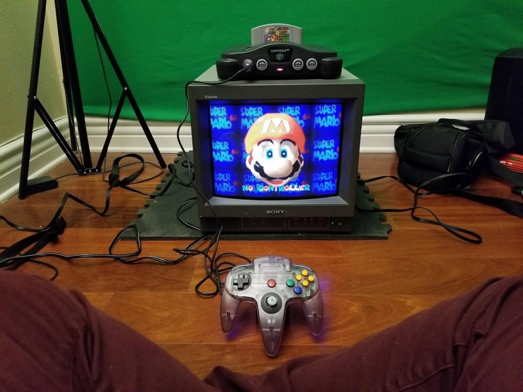 Nintendo 64 on top of tv with Mario on the screen