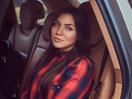 Caucasian woman wearing a black and red flannel shirt sitting in a car not smiling