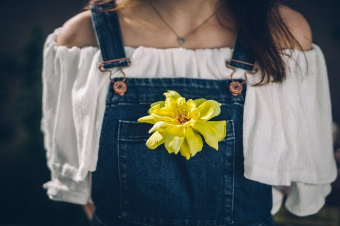 woman wearing denim blue overalls with a yellow flower in the pocket