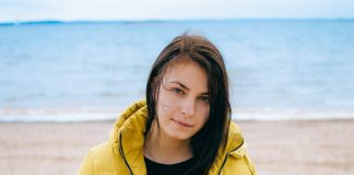 Woman wearing a yellow puffer jacket on the beach