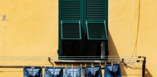 Row of bootcut jeans hanging on washing line outside apartment