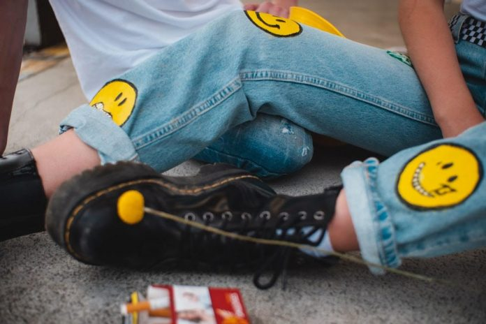 A woman wearing doc martens boots with jeans with smiley face patches