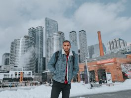A man in Toronto wearing a denim jacket in front of a city skyline